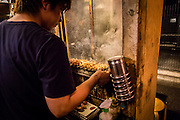 On one of the many restaurants in Yurakucho, a man grills some yakitori skewers.