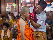 "06 APRIL 2015 - CHIANG MAI, CHIANG MAI, THAILAND: Family members help boys scrub off their make up during the ordination of the boys on the last day of the three day long Poi Song Long Festival in Chiang Mai. The boys spend the first two days of the ceremony dressed as royalty in ornate outfits before getting into the austere monks' robes. The Poi Sang Long Festival (also called Poy Sang Long) is an ordination ceremony for Tai (also and commonly called Shan, though they prefer Tai) boys in the Shan State of Myanmar (Burma) and in Shan communities in western Thailand. Most Tai boys go into the monastery as novice monks at some point between the ages of seven and fourteen. This year seven boys were ordained at the Poi Sang Long ceremony at Wat Pa Pao in Chiang Mai. Poy Song Long is Tai (Shan) for ""Festival of the Jewel (or Crystal) Sons.   PHOTO BY JACK KURTZ"