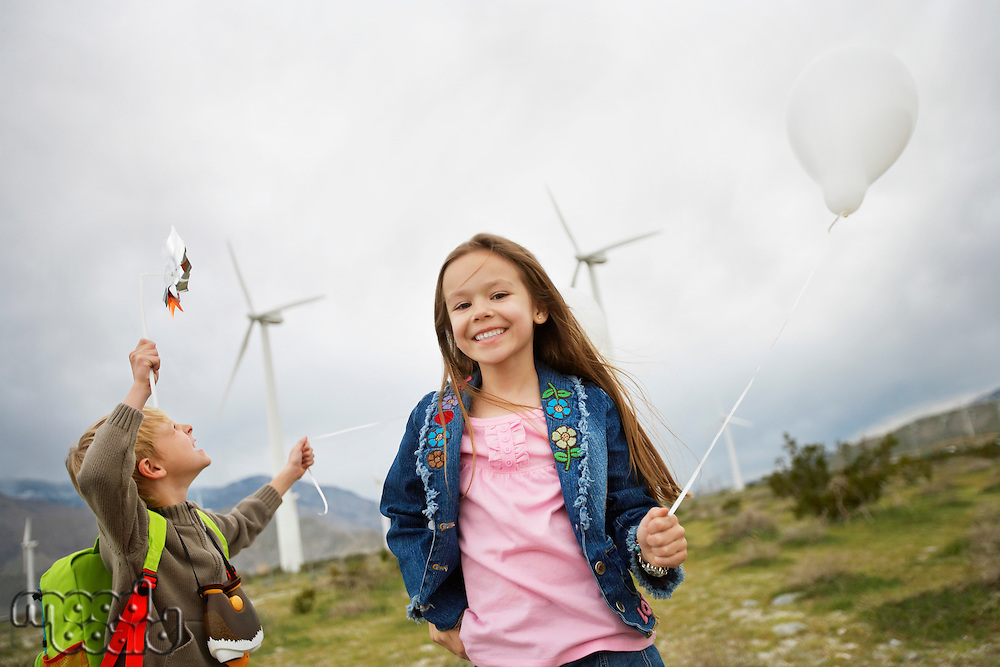 Boy and girl (5-9) playing with balloons at wind farm