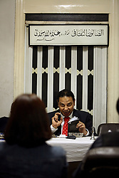 Ala'a Al-Aswany, a prominent Egyptian writer and founding member of the political movement Kefaya, encourages a young writer during his literary salon in Cairo, Egypt on April 4, 2008. Trained as a dentist in Cairo and Chicago, al-Aswany has contributed numerous articles to Egyptian newspapers on literature, politics, and social issues. His second novel, The Yacoubian Building, an ironic depiction of modern Egyptian society, has been widely read in Egypt and throughout the Middle East. It was translated into English and was adapted into a film (2006) and a television series (2007) of the same name. Chicago, Al-Aswany's latest novel, is set in the American city where he had attended college.
