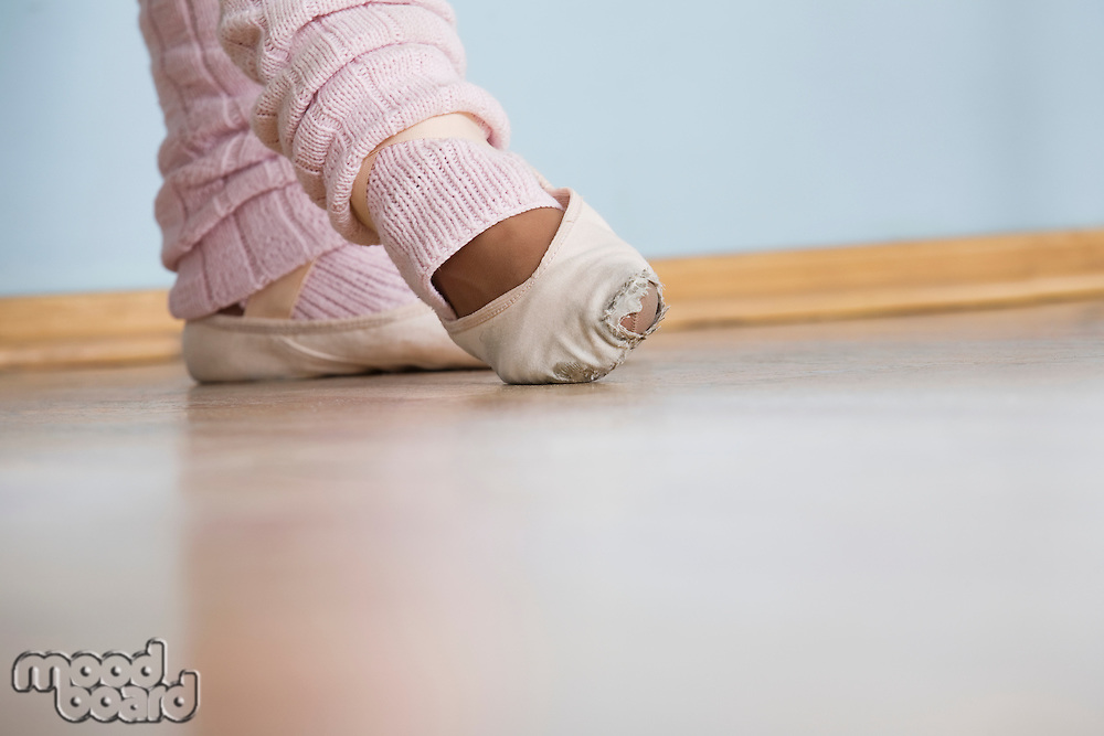 Young woman positions feet in ballet rehearsal
