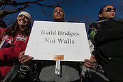A man holds a sign saying Build Bridges Not Walls at a protest march and rally organised by the Alliance for an Inclusive America group against the perceived anti-Muslim and anti-foreigner immigration policies of President Donald Trump, Shibuya, Tokyo, Japan. Sunday February 12th 2017. The Alliance of an Inclusive America is a multi-faith non-partisan group. About 250 Americans, other ex-pats and japanese people took part in the march to show people around the world they reject the Executive Order President Trump enacted at the end of January, indefinitely suspending the resettlement of Syrian refugees and temporarily banning people from seven majority Muslim countries from entering the United States.