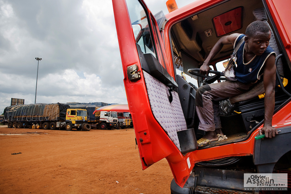 A man looks out from the driver seat of a large truck at the Terminal du Sahel, a large truck terminal in Lome, Togo on Wednesday October 1, 2008.