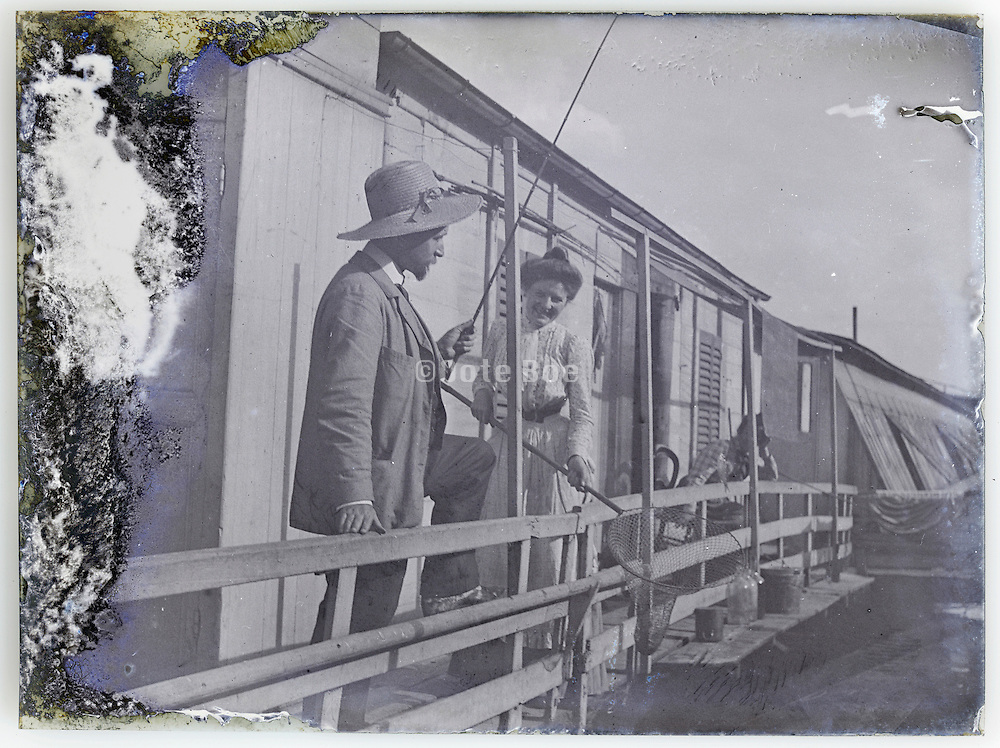 vintage eroding glass plate with couple fishing from the houseboat