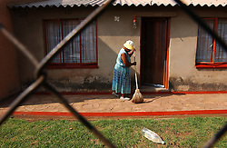 JOHANNESBURG, SOUTH AFRICA - APRIL-28-2004 - A woman sweeps her front porch in the Soweto Township of Johannesburg. The plastic bottle, which reflects the suns light, is left in the front yard top keep dogs away. (PHOTO © JOCK FISTICK)