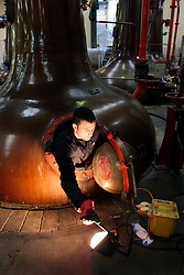 UK SCOTLAND DUFFTOWN 24JUN04 - Maintenance engineer George Singer peeks out from a copper still at the Glenfiddich destillery in Dufftown, Scotland, the world's Whisky capital. Glenfiddich is the largest family-owned single malt Whisky destillery worldwide with 80% of production destined for export.....jre/Photo by Jiri Rezac for Frankfurter Allgemeine....© Jiri Rezac 2004....Contact: +44 (0) 7050 110 417..Mobile:  +44 (0) 7801 337 683..Office:  +44 (0) 20 8968 9635....Email:   jiri@jirirezac.com..Web:    www.jirirezac.com....© All images Jiri Rezac 2004 - All rights reserved.
