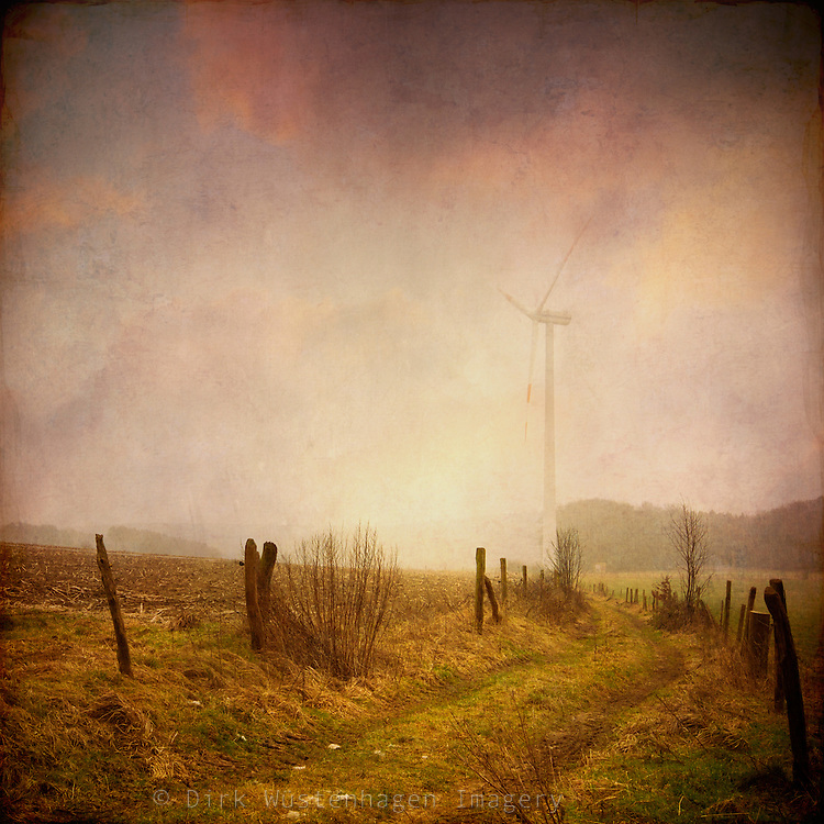 Rural area in the Bergisches Land/Germany on a frosty winter day with a wind turbine in the haze