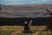With huge lixiviation pads in the background and nearing her land, an indigenous farmer cleans barley near Yanacocha gold mine in Peru, Sunday, October, 2015.(Hlaea Media/ Dado Galdieri)