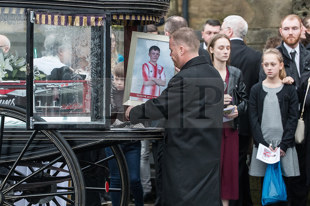 © Licensed to London News Pictures . 20/12/2017. Manchester, UK. Sam's photo is placed inside the hearse outside the church after the service . The funeral of 14-year-old Sam Berkley at Christ Church in Denton , East Manchester . Mourners wear red and white , the colours of Hattersley FC , for whom Berkley played . Amongst their number are pupils and friends from Audenshaw School . Berkley died after being hit by a grey BMW near junction 3 of the M67 in Hyde , East Manchester , on 1st December 2017 . Photo credit: Joel Goodman/LNP
