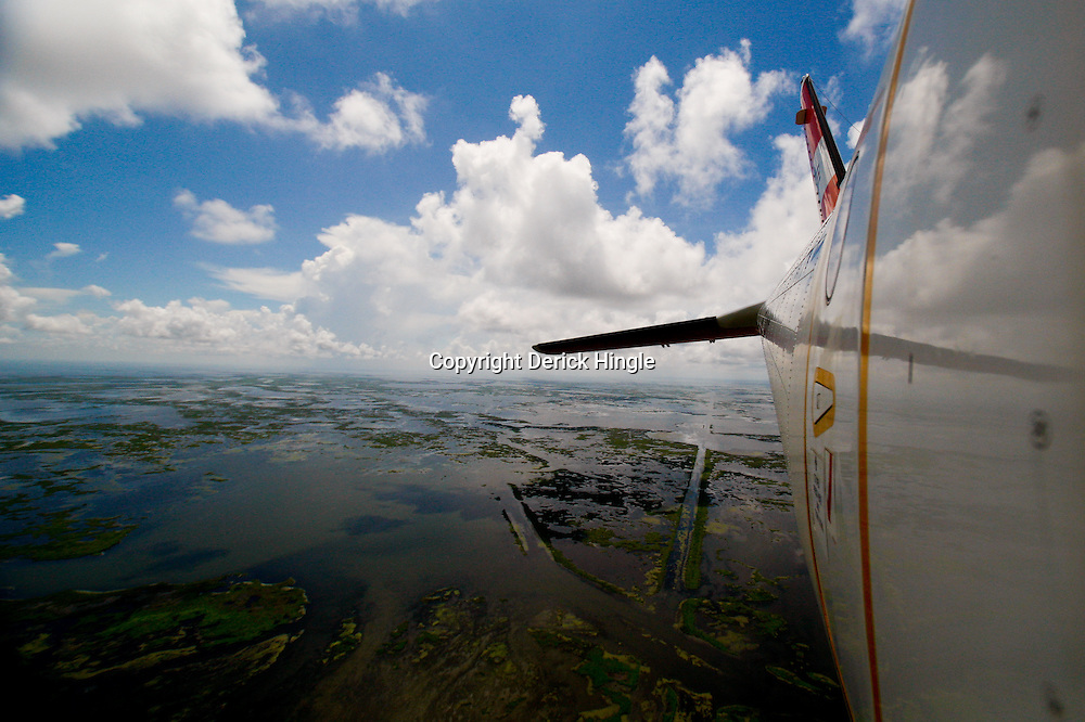 Canals created for navigation and oil and gas pipelines cut through the marsh are seen through a window in a U.S. Coast Guard C-144 flight over the coast of Louisiana, U.S., on Monday, July 26, 2010. Photographer: Derick E. Hingle/Bloomberg