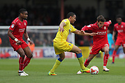 AFC Wimbledon defender Darius Charles (32) weaves between Swindon Town striker Jonathan Obika (9) and Swindon Town midfielder John Goddard (10) during the EFL Sky Bet League 1 match between Swindon Town and AFC Wimbledon at the County Ground, Swindon, England on 14 April 2017. Photo by Stuart Butcher.