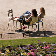Two young women sitting in sun reading newspaper in the Jardin du Luxembourg, Paris France<br />