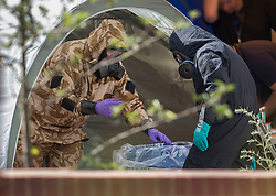 © Licensed to London News Pictures. 06/07/2018. Amesbury, UK. Police officers in protective suits and gas masks decontaminate after gathering evidence inside a house in Muggleton Road, Amesbury where a couple, named locally as Dawn Sturgess, 44, and her partner Charlie Rowley, 45, were taken ill on Saturday 30th June 2018. Police have confirmed that the couple have been in contact with Novichok nerve agent. Former Russian spy Sergei Skripal and his daughter Yulia were poisoned with Novichok nerve agent in nearby Salisbury in March 2018. Photo credit: Peter Macdiarmid/LNP