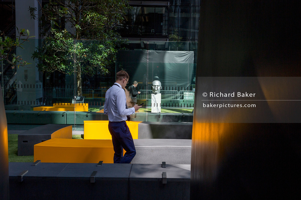 An office worker in shortsleeves outside outside the Leadenhall Building during the 2018 heatwave in the City of London, the capital's financial district, on 24th July 2018, in London, England.