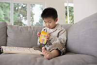 Smiling Boy on sitting barefooted on Sofa with Coloring Book