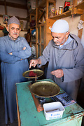TALIOUINE, MOROCCO - October 26th 2015 - Saffron trader weighs saffron for a customer at his market stall in the Taliouine market, Souss Massa Draa, Morocco