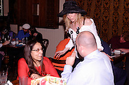 """Tammy Schaff (standing) talks to audience members during Mayhem & Mystery's production of """"Fashion Friction"""" at the Spaghetti Warehouse in downtown Dayton, Monday, March 21, 2011."""