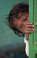 Child peeping behind the door.