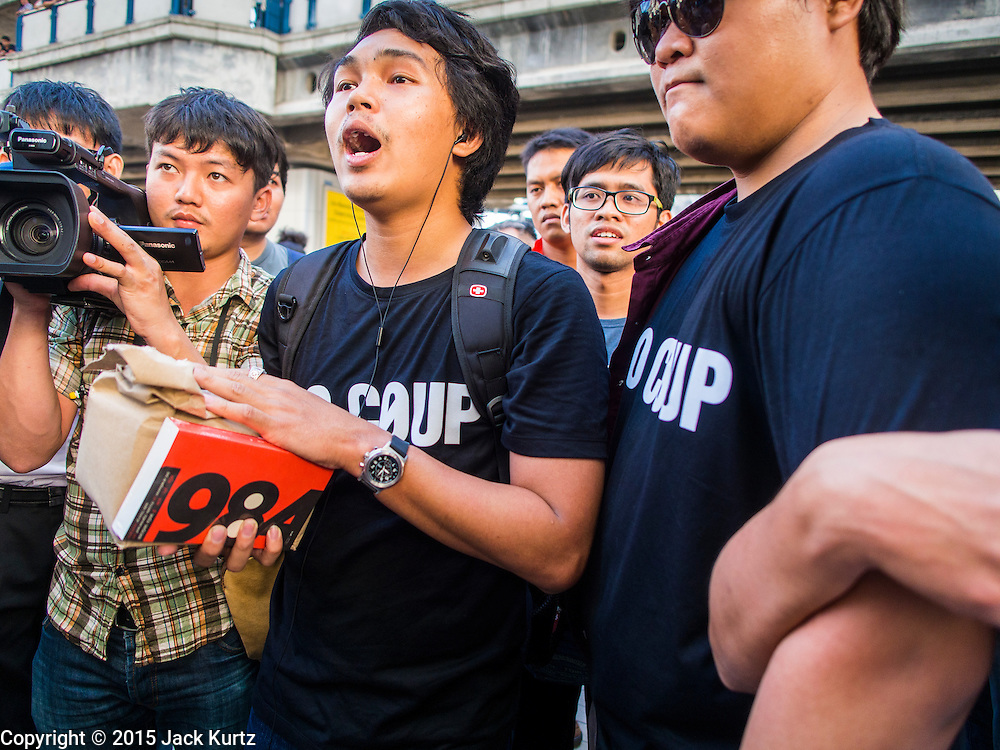 "14 FEBRUARY 2015 - BANGKOK, THAILAND:  An anti-coup protestors hand out copies of ""1984"" during a protest against the coup. Handing out or reading ""1984"" in public can be grounds for arrest under Thailand's martial law. Dozens of people gathered in front of the Bangkok Art and Culture Centre in Bangkok Saturday to hand out red roses and copies of George Orwell's ""1984."" Protestors said they didn't support either Red Shirts or Yellow Shirts but wanted a return of democracy in Thailand. The protest was the largest protest since June 2014, against the military government of General Prayuth Chan-Ocha, who staged the coup against the elected government. Police made several arrests Saturday afternoon but the protest was not violent.     PHOTO BY JACK KURTZ"