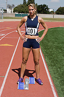Female athlete standing next to starting block