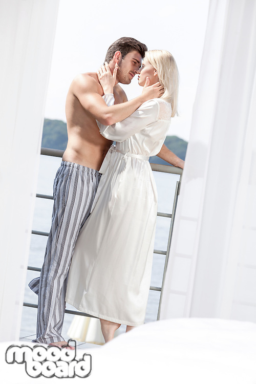 Side view of romantic young couple in sleepwear spending quality time on hotel balcony