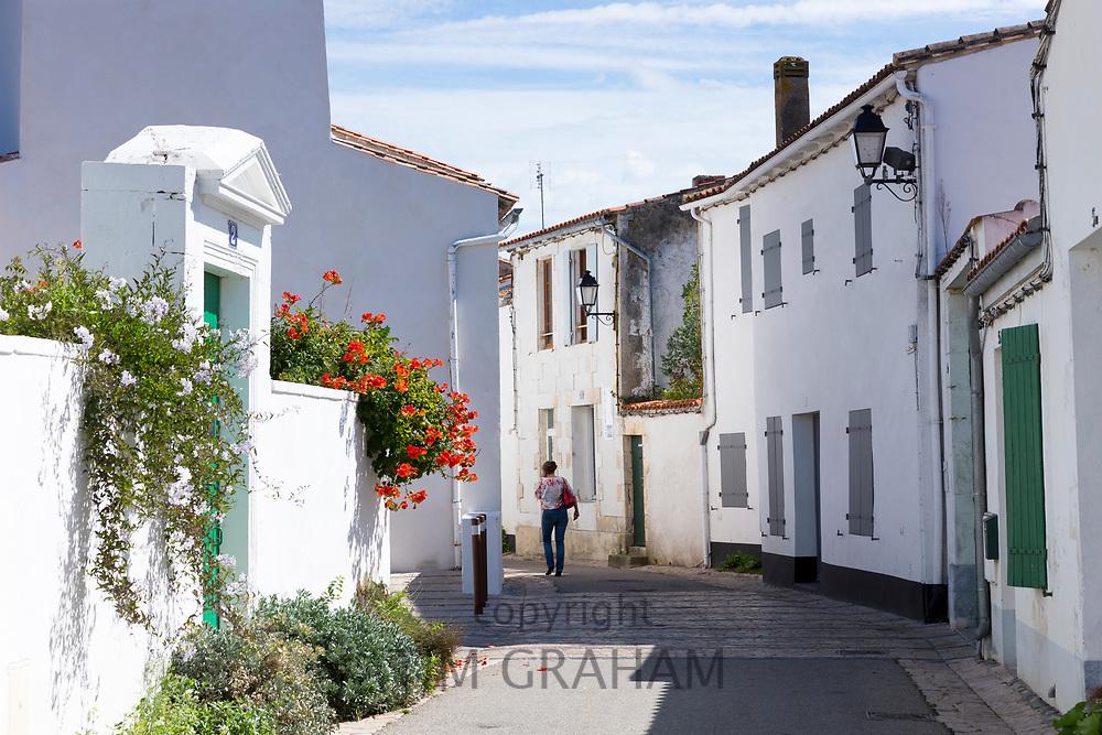 Woman walking typical street scene quaint houses traditional architecture, Les Portes en Re, Ile de Re, France