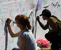 London, June 15th 2017. Mountains of food and clothing donated to the many people who have lost everything and been made homeless in the Grenfell Tower fire of June 14th, by generous Londoners are categorised and stored on a basketball court at the Westway Sports Centre and other locations near to the scene of the fire. PICTURED: Women write messages of condolence on a wall near Latymer Road tube station.