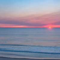 Sun just peeks over the horizon during sunrise at Cape Cod National Seashore.