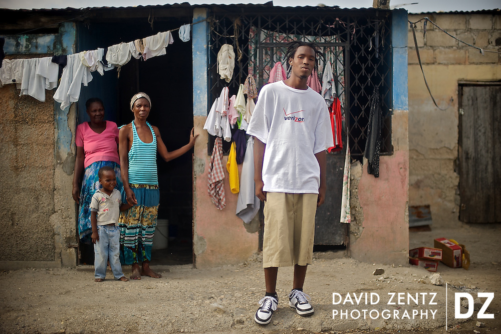 Rap kreyol artist 2Double stands in front of the narrow cement home he shares with his mother and 3-year-old son, pictured at left at a neighbor's (in pink) home on July 19, 2008. He says he hopes his music can lift his family out of the abject poverty that plagues the majority of the citizens of Haiti.