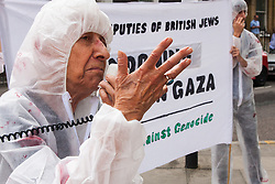 London, August 4th 2014. A woman from British Jews Against Genocide accuses the media of a pro-Israel bias during a protest outside the offices of the Board of Deputies of British Jews, as the Israeli attacks on Gaza continue.