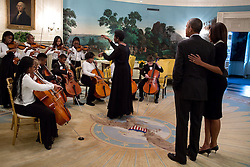 President Barack Obama and First Lady Michelle Obama listen to the DC Youth Orchestra in the Diplomatic Reception Room prior to a reception celebrating Black History Month in the East Room of the White House, Feb. 26, 2015. (Official White House Photo by Pete Souza)<br /> <br /> This official White House photograph is being made available only for publication by news organizations and/or for personal use printing by the subject(s) of the photograph. The photograph may not be manipulated in any way and may not be used in commercial or political materials, advertisements, emails, products, promotions that in any way suggests approval or endorsement of the President, the First Family, or the White House.