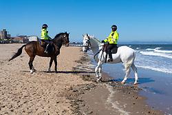 Portobello, Scotland, UK. 19 April 2020. Mounted police horses Logie and Edinburgh - in white , patrol the promenade and beach at Portobello on sunny Sunday afternoon. Iain Masterton/Alamy Live News
