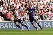 Tottenham Hotspur forward Harry Kane tackles Sunderland Defender Patrick Van Aanholt during the Barclays Premier League match between Sunderland and Tottenham Hotspur at the Stadium Of Light, Sunderland, England on 13 September 2015. Photo by Simon Davies.
