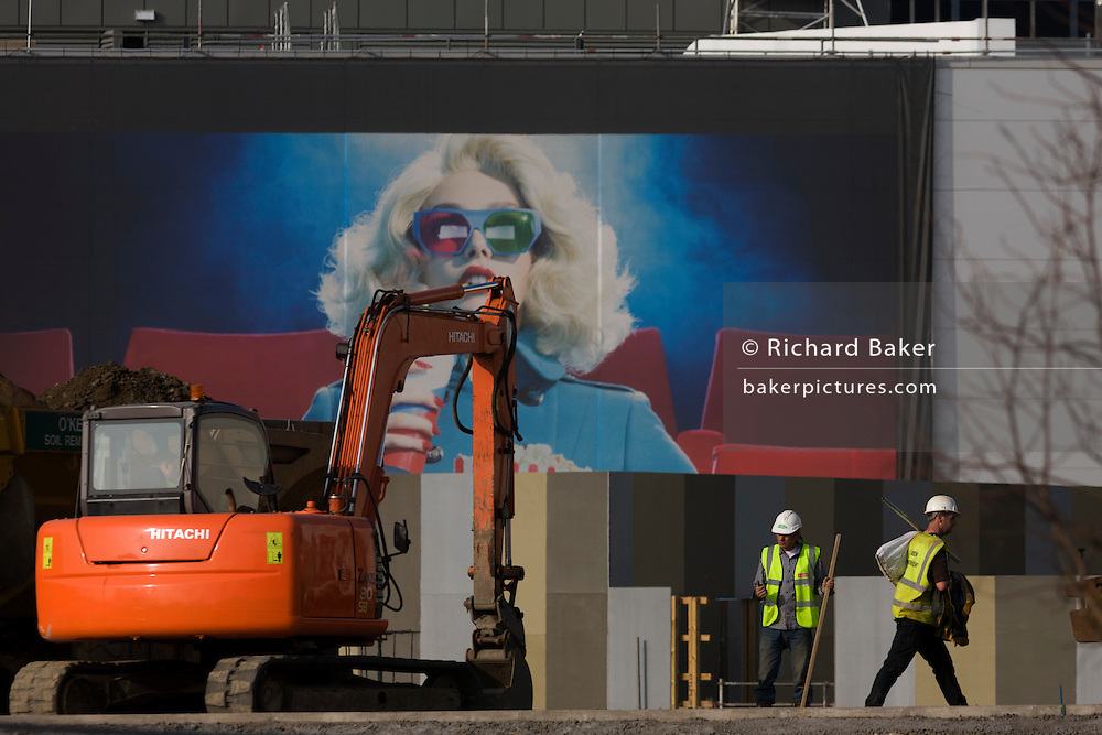 An excavator and aspirational poster on wall during building of 2012 Olympic Westfield City shopping centre, Stratford. A glamorous woman sips a drink with a straw representing the good times - wealth and beauty and the symbols of affluence - while the working men are seen small in comparison, the downtrodden Man. The £1.45bn complex houses more than 300 shops, 70 restaurants, a 14-screen cinema, three hotels, a bowling alley and the UK's largest casino. It will provide the main access to the Olympic park for the 2012 Games and a central 'street' will give 75% of Olympic visitors access to the main stadium so retail space and so far 95% of the centre has been let. It is claimed that up to 8,500 permanent jobs will be created by the retail sector..