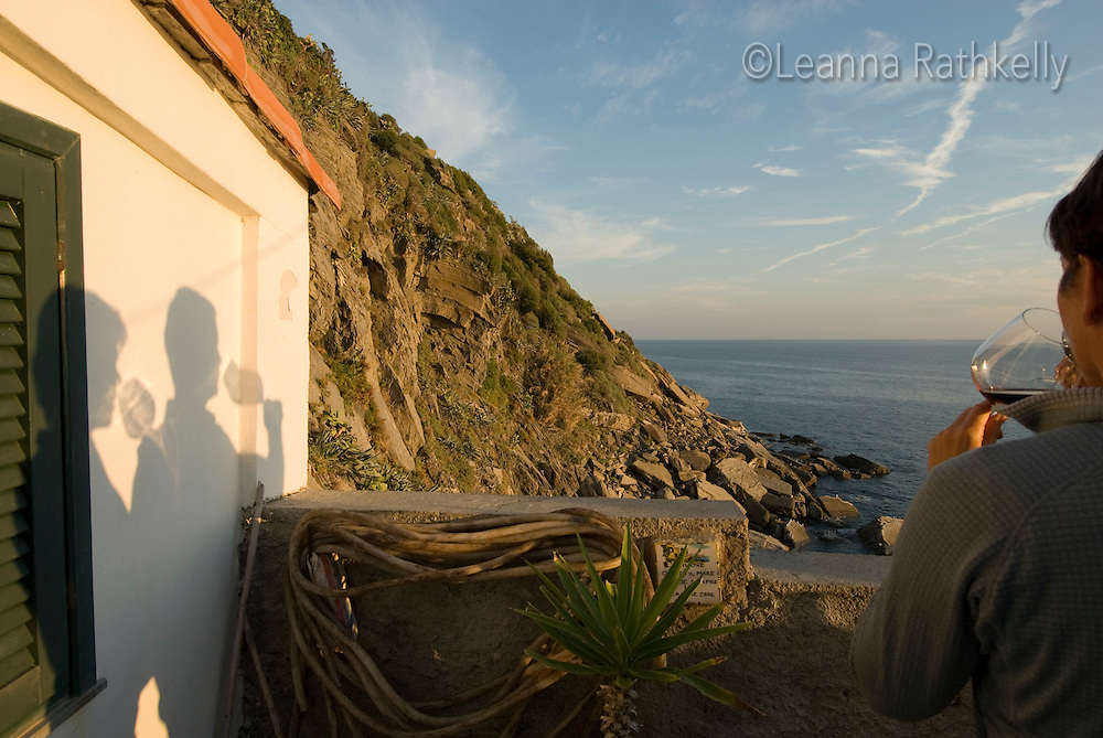 Shadows on the wall of man and woman drinking wine, sunset in Vernazza, Cinque Terre, Italy.
