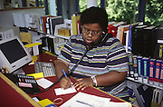 reference librarian at desk in library talking on phone; making notes