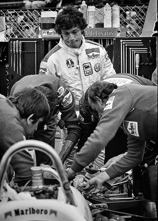 Andrea deCesaris can only grimace as Marlboro Alfa Romeo race mechanics rush to solve a transmission malfunction within minutes of the start of the 1982 Detroit Grand Prix. <br />