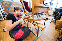A furniture upholstery student refurbishing an old chair.