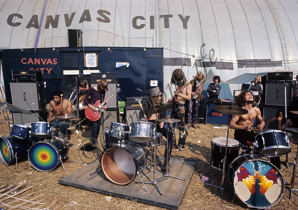 Pink Fairies and Hawkwind - Outside Canvas City.-.Hawkwind are seen here, behind the Pink Fairies, outside Canvas City - One of the performance tents. David Brock still tours with Hawkwind to this day, whilst Nik Turner offers a rival experience with his band Hawklords. Lemmy (Motorhead)didn't join the band until later, but reckoned Turner always looked so great that it was like being on stage with a Viking berserker. Thomas Crimble &  Nik Turner also tour with Space Rictual.