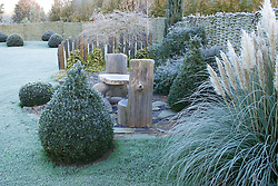 Seating area with rustic table and chair. Topiary of clipped box and yew balls. Slate pillars used as screen. Cortaderia selloana 'Pumila' - Pampas grass. Frosty winter's morning. Design: John Massey, Ashwood Nurseries