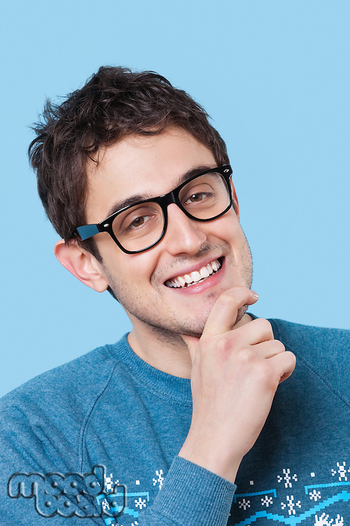 Portrait of happy young man with hand on chin over blue background