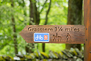 Signpost for public footpath, bridleway and cycleway towards Grasmere in the Lake District, Cumbria, England
