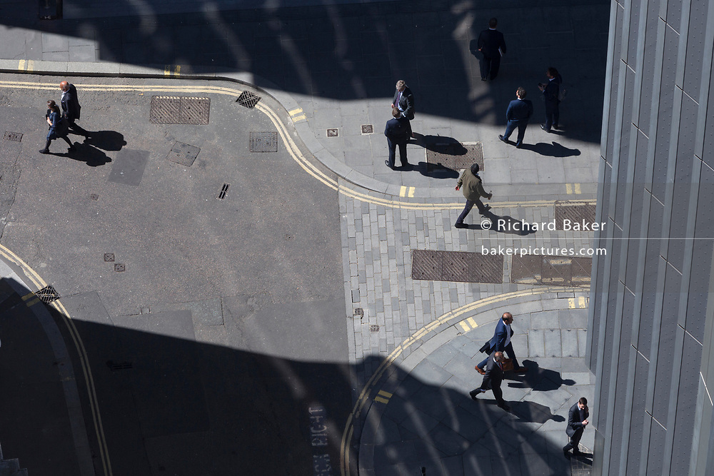 Looking down from an aerial view towards small business figures walking through sunlight in the City of London, the capital's ancient financial district, on 13th May, in London, England.