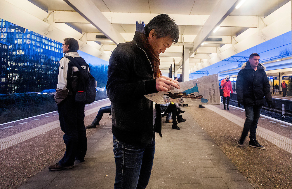 Nederland, Amsterdam, 8 dec 2014<br /> Ns-station Amsterdam Zuid. Man staat gratis krant metro te lezen.<br /> Foto: (c) Michiel Wijnbergh