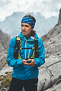 Portrait of a trail runner using GPS on a rainy day close to Collado Jermoso, Leon, Spain Trail runner running uphill in Collado Jermoso, Picos de Europa National Park, Spain