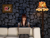 Young woman using laptop sitting on sofa