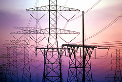 Stock photo of a group of power line structures silhouetted at sunset