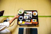 NARA, JAPAN,  Traditionnal Japanese breakfast in a ryokan - A woman light on the fire to make warm the soup of soy milk and tofu  ;  JULY 2005 [FR] Une femme allume le bruleur pour chaffer la soupe du petit dejeuner traditionnel Japonais servi sur les tatami d'un ryokan à Nara.