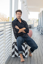 good looking man sitting on a motel deck
