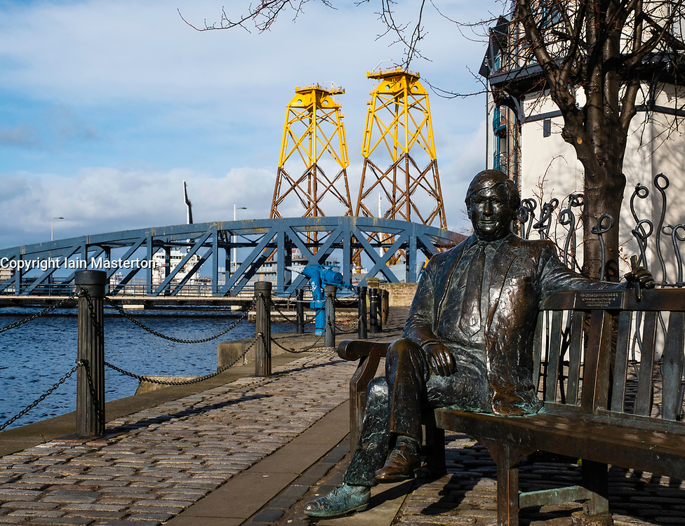 Statue of Sandy Irvine Robertson on bench on waterside at Leith in Edinburgh, Scotland, United Kingdom